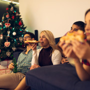 Shot of a friends eating pizza, drinking beer and watching tv.
